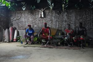 Shows Moughenda and his Bwiti brothers sitting in temple